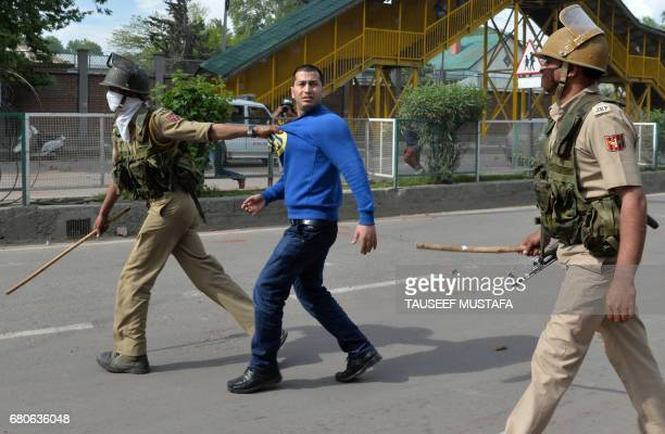 Indian police arrest a Kashmiri youth during clashes between Kashmiri students and Indian government forces in central Srinagar's Lal Chowk on May 9...