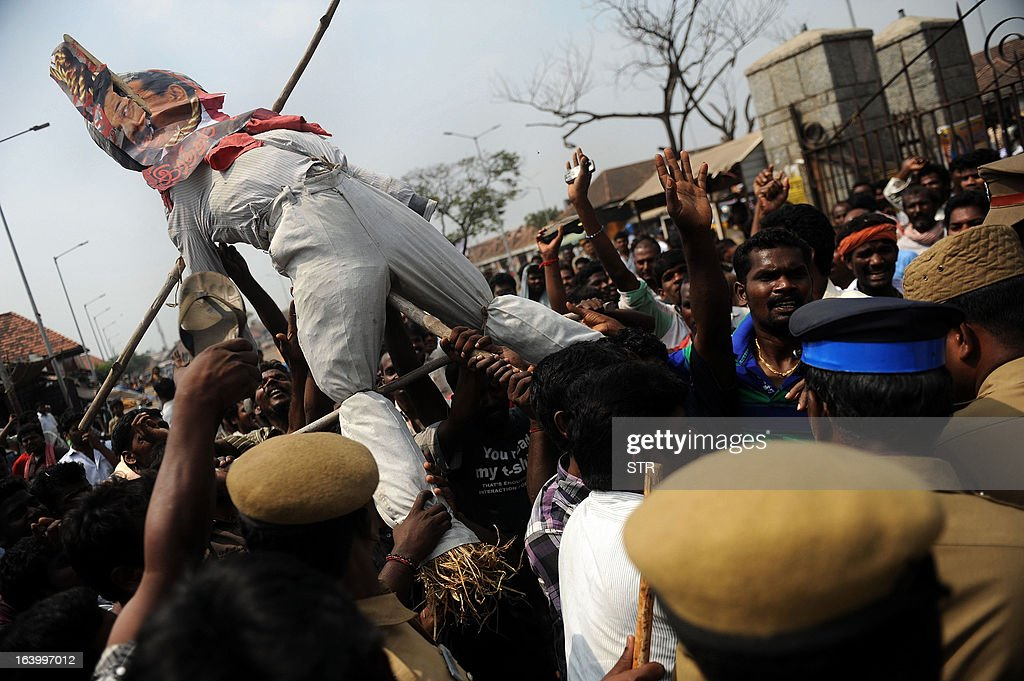 Indian police confront vendors from the Koyembedu market as they carry an effigy of Sri Lankan President Mahinda Rajapakase wearing a mask of his face with a rope around his neck during a protest seeking justice for the victims of the Sri Lankan war and trial of war criminals, in Chennai on March 19, 2013. The Dravida Munnetra Kazhagam (DMK), a regional party based in South India, announced Tuesday that it was withdrawing from the national ruling coalition, weakening the government which was already a minority in parliament. The DMK had been pressuring the government to condemn Sri Lanka over alleged war crimes against ethnic minority Tamils during the neighbouring island's civil war.