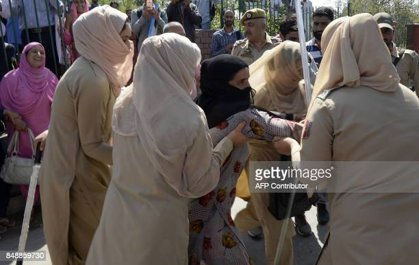 Indian police detain a Kashmiri 'Anganwadi' a government sponsored child and mother care worker during an antigovernment protest in Srinagar on...