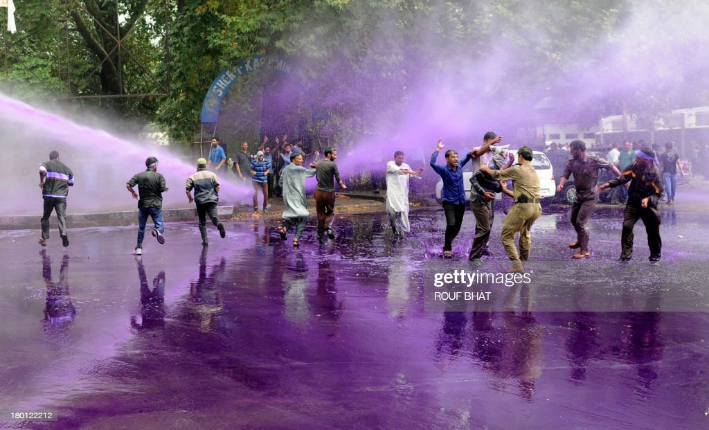 Indian police detain a Kashmiri government employee as others run during a protest as riot police spray purple-dyed water cannon in Srinagar on September 9, 2013. Indian police detained dozens of government employees, who have been demanding regularisation of contractual jobs and an increase in retirement age.They also demanded an impartial probe into the killing of four people by Indian paramilitary soldiers on September 7,and killers should be exposed. AFP PHOTO/Rouf BHAT