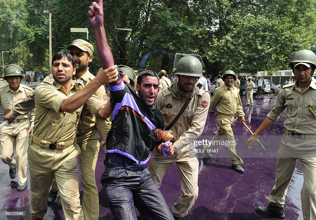 Indian police detain a Kashmiri government employee during a protest as riot police spray purple-dyed water cannon in Srinagar on September 9, 2013. Indian police detained dozens of government employees, who have been demanding regularisation of contractual jobs and an increase in retirement age.They also demanded an impartial probe into the killing of four people by Indian paramilitary soldiers on September 7,and killers should be exposed. AFP PHOTO/Rouf BHAT