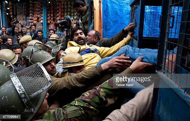 Indian police detain a supporter of Jammu and Kashmir Liberation Front during a protest against the expulsion of over 60 students from the College of...