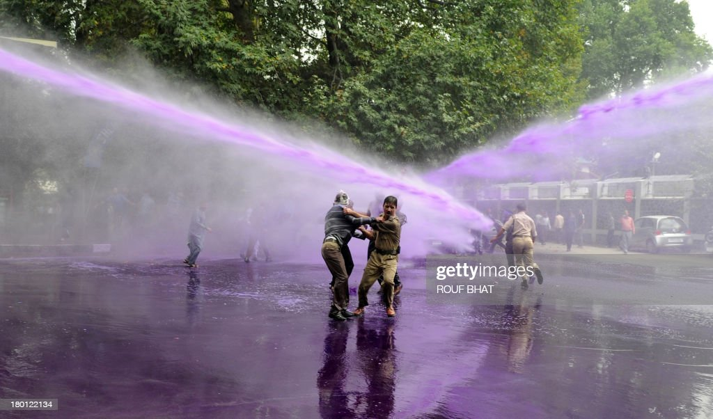 Indian police detain Kashmiri government employees during a protest as riot police spray purple-dyed water cannon in Srinagar on September 9, 2013. Indian police detained dozens of government employees, who have been demanding regularisation of contractual jobs and an increase in retirement age.They also demanded an impartial probe into the killing of four people by Indian paramilitary soldiers on September 7,and killers should be exposed. AFP PHOTO/Rouf BHAT