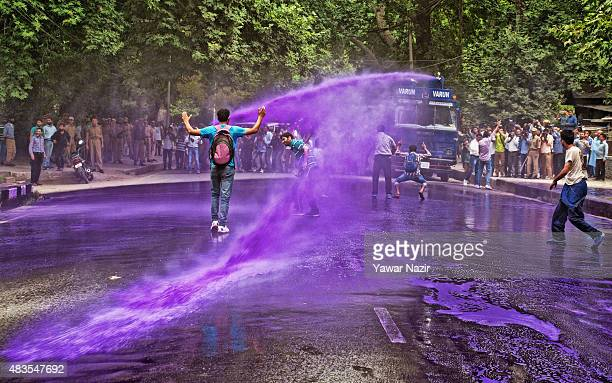 Indian police fire a jet of purple dyed chemical water from their water canon at Kashmiri government employee during a protest against the government...