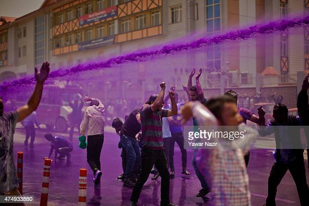 Indian police fire a water cannon of purple dyed chemical water at Kashmiri daily wage employees during a protest against the government on May 28...