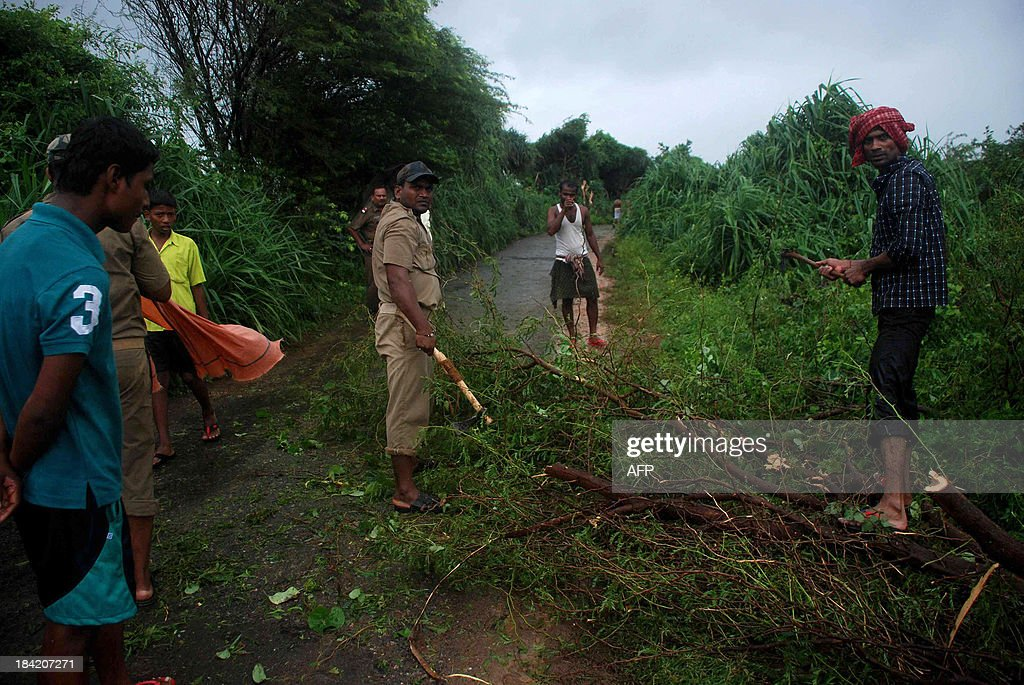 Indian police force members and volunteers clear branches from the village road due to heavy cyclonic wind with rain in Badabandha Village near Gopalpur, about 195 kilometers south from eastern city Bhubaneswar on October 12, 2013. Nearly half a million people have been evacuated from India's impoverished east coast ahead of a massive cyclone expected to make landfall on October 12 evening, disaster officials said.