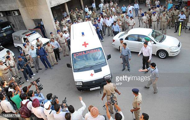 Indian police guard an ambulance carrying the body of Pakistani prisoner Sanaullah Ranjay in Chandigarh on May 9 as it heads to the airport to...