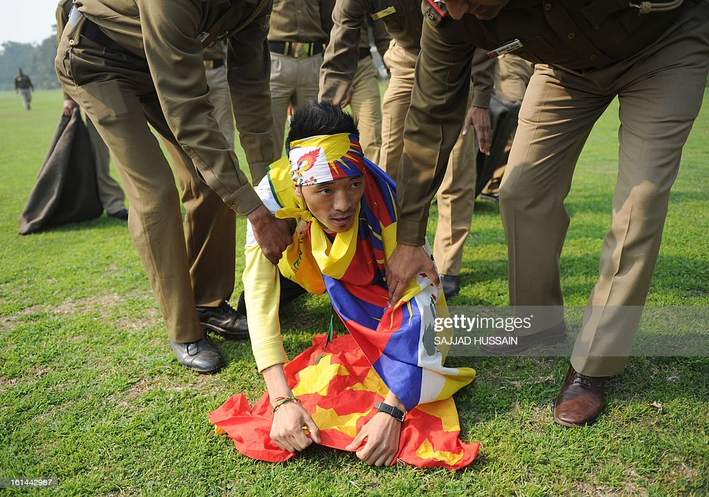 Indian police officers detain a demonstrating Tibetan exile as he attempts to tear a Chinese flag outside the Chinese embassy during Losar, the Tibetan new year, in New Delhi on February 11, 2013. Lobsang Sangay, the Tibetan prime minister in exile, has called for traditional Losar (the Tibetan new year) celebrations to be shelved as a mark of respect to the nearly 100 people who have set themselves on fire in the last three years.