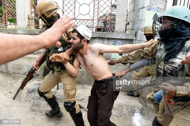 Indian police officials arrest a Kashmiri youth during clashes after Friday congregational prayers outside The Jamia Masjid in Srinagar on May 19...