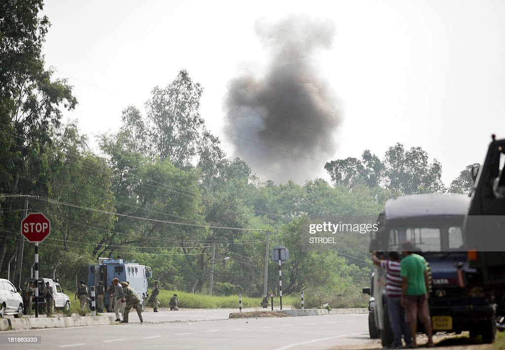 Indian police officials, civilians and army personnel look on as smoke rises during an attack by militants on an army camp at Mesar in Samba District, some 20kms south-east of Jammu on September 26, 2013. Militants disguised as soldiers killed seven people in an attack on a police base in Indian Kashmir, days before long-awaited talks between the leaders of India and Pakistan, police said. The attackers then escaped after hijacking a truck and were now engaged in a fierce gun battle with Indian troops in Samba district of the region near the border with Pakistan, the NDTV news network and other local media reported. AFP PHOTO/STR