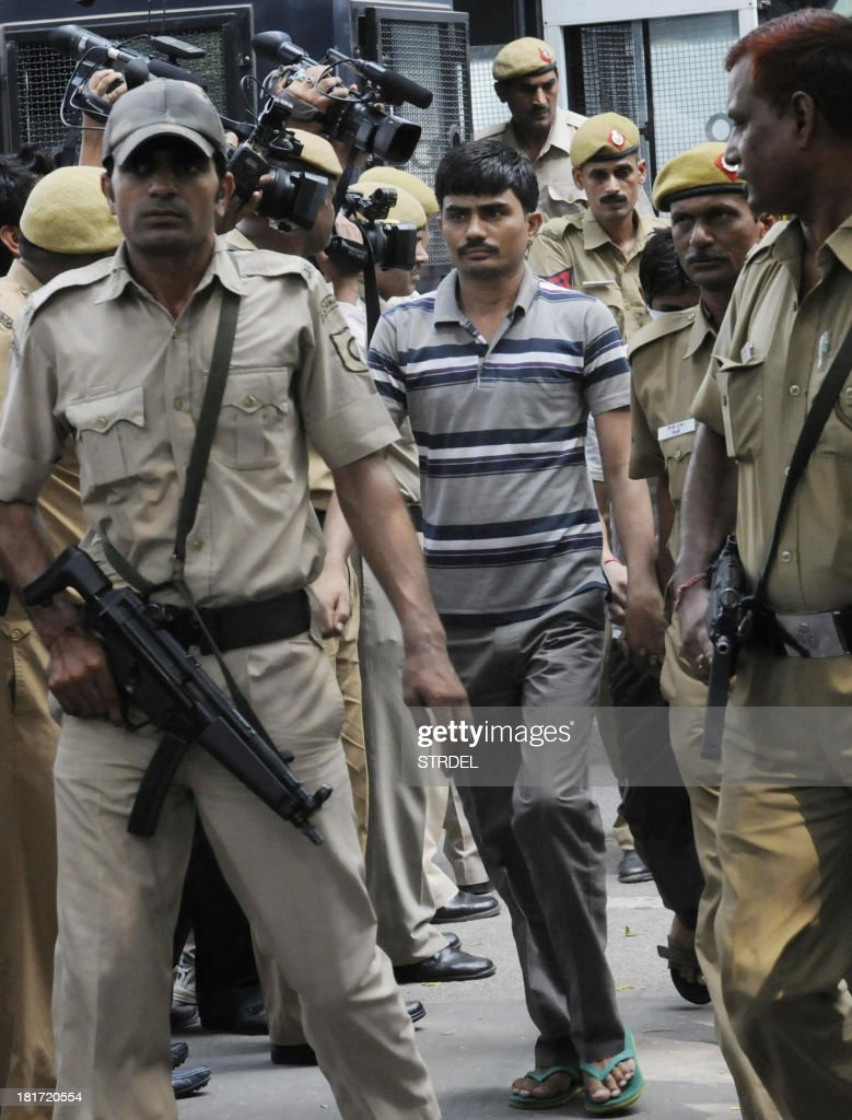Indian police officials escort Akshay Thakur, one of those convicted in the Delhi gangrape case, to an appearance at the High Court in New Delhi on September 24, 2013. An Indian judge on September 13, sentenced to death four men convicted of the fatal gang rape of a student on a New Delhi bus last December, fulfilling the last wish of the 23-year-old victim.