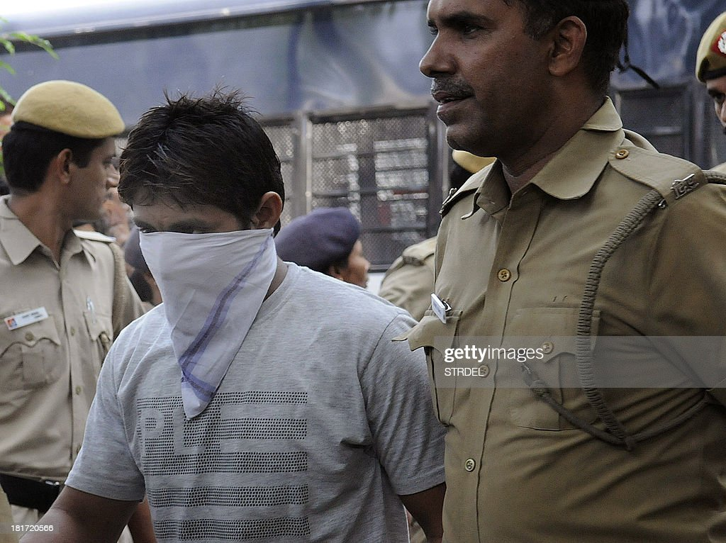 Indian police officials escort Pawan Gupta, one of those convicted in the Delhi gangrape case, to an appearance at the High Court in New Delhi on September 24, 2013. An Indian judge on September 13, sentenced to death four men convicted of the fatal gang rape of a student on a New Delhi bus last December, fulfilling the last wish of the 23-year-old victim.