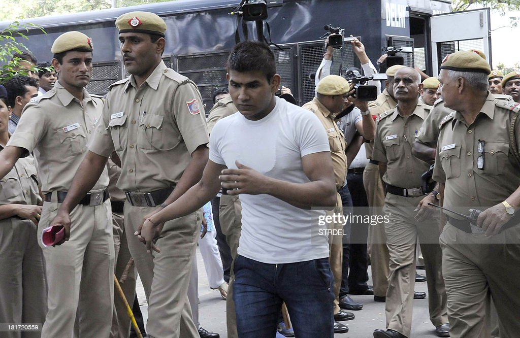 Indian police officials escort Vinay Sharma, one of those convicted in the Delhi gangrape case, to an appearance at the High Court in New Delhi on September 24, 2013. An Indian judge on September 13, sentenced to death four men convicted of the fatal gang rape of a student on a New Delhi bus last December, fulfilling the last wish of the 23-year-old victim. AFP PHOTO/STR