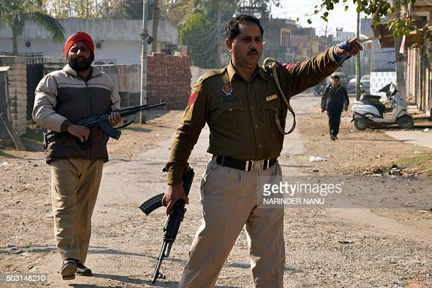 Indian police officials gesture as they stand alert outside an airforce base in Pathankot on January 2 during an ongoing attack on the base in the...