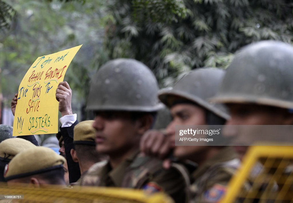 Indian police officials look on as a protester carrying a banner moves behind them during a rally in New Delhi on December 30, 2012, following the cremation of a gangrape victim in the Indian capital. The victim of a gang-rape and murder which triggered an outpouring of grief and anger across India was cremated at a private ceremony, hours after her body was flown home from Singapore. A student of 23-year-old, the focus of nationwide protests since she was brutally attacked on a bus in New Delhi two weeks ago, was cremated away from the public glare at the request of her traumatised parents. AFP PHOTO/ ANDREW CABALLERO-REYNOLDS