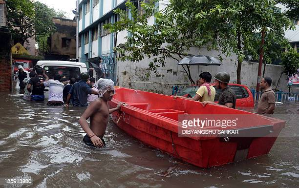 Indian Police officials pull a boat hrough waterlogged streets as others push a police vehicle in Kolkata on October 26 2013 Persistent rain for the...