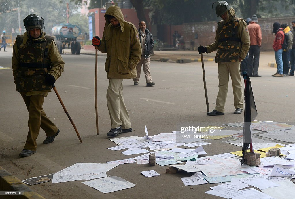 Indian police officials read posters left by protestors in New Delhi on January 2, 2013. The family of an Indian gang-rape victim said that they would not rest until her killers are hanged as police finalised their investigation before charges are laid against suspects this week. As the ruling Congress party reportedly pushed for tougher punishments for sex crimes, including chemical castration, authorities in New Delhi launched a hotline to improve safety for women in a city dubbed 'India's rape capital'. . AFP PHOTO/RAVEENDRAN