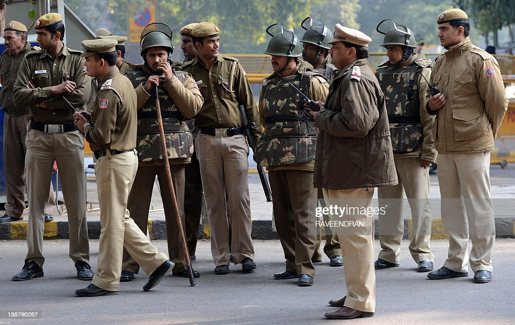 Indian police officials stand alert on a street in New Delhi on December 29, 2012, as Indian leaders appealled for calm fearing fresh outbursts of protests after the death of a gang-rape victim. New Delhi's top police officer and chief minister have urged people to mourn the death of a gang-rape victim in a peaceful manner as large parts of the city-centre were sealed off. The calls for calm came after an Indian woman who was gang-raped on a New Delhi bus died in a Singapore hospital after suffering severe organ failure. AFP PHOTO/RAVEENDRAN