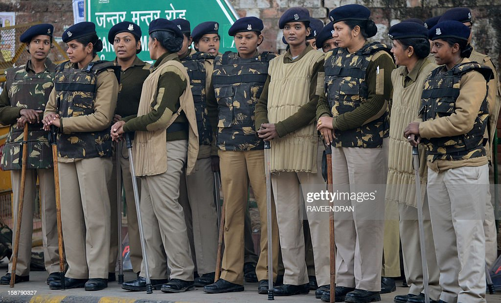 Indian police officials stand alert on a street in New Delhi on December 29, 2012, as Indian leaders appealled for calm fearing fresh outbursts of protests after the death of a gang-rape victim. New Delhi's top police officer and chief minister have urged people to mourn the death of a gang-rape victim in a peaceful manner as large parts of the city-centre were sealed off. The calls for calm came after an Indian woman who was gang-raped on a New Delhi bus died in a Singapore hospital after suffering severe organ failure.