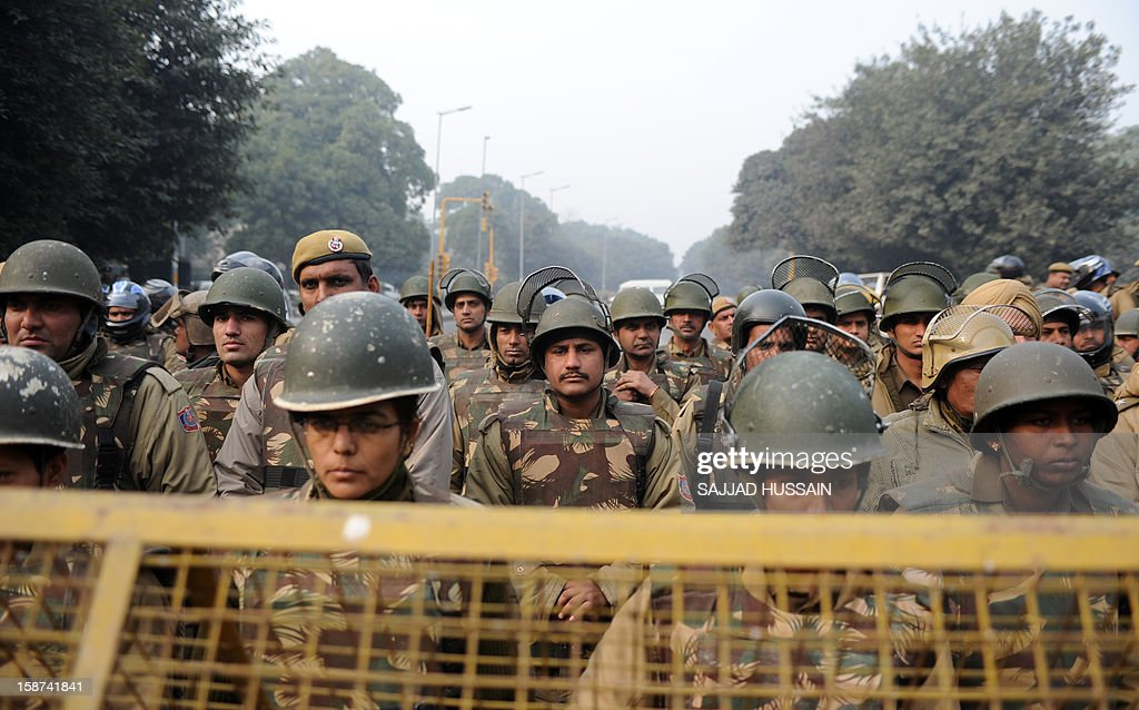 Indian police officials stand behind a barrier as demonstrators move towards India Gate in New Delhi on December 27, 2012, during a protest calling for better safety for women following the rape of a student in the Indian capital. Protests across India over the last week against sex crimes have denounced the police and government, with the largest in New Delhi at the weekend prompting officers to cordon off areas around government buildings. One policeman was killed and more than 100 people injured in the violence. AFP PHOTO/SAJJAD HUSSAIN