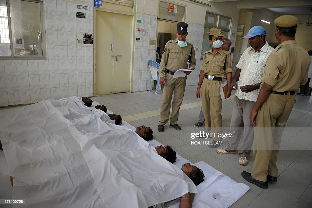 Indian police officials stand beside the bodies of those killed in a building collapse, in the mortuary at Gandhi Hospital in Secunderabad, the twin city of Hyderabad on July 8, 2013. A two-storey hotel collapsed in the southern Indian city of Secunderabad, killing at least 12 people and injuring 16 others, police said. Rescue workers were searching through tonnes of rubble for those still trapped after the incident in Andhra Pradesh state, local police official K. Satyanarayana told AFP. AFP PHOTO/Noah SEELAM