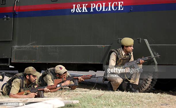 Indian police officials take position behind a vehicle during an attack by militants on an army camp at Mesar in Samba District some 20kms southeast...