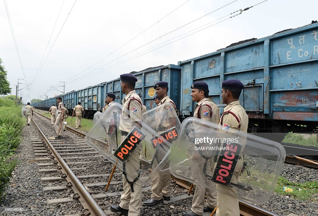 Indian police patrol railway tracks damaged by rioters on the outskirts of Ahmedabad on August 26 2015 Thousands of Indian paramilitary troops have...