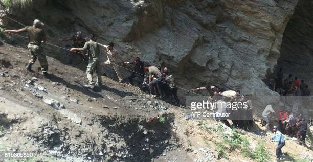 Indian police personnel and locals carry injured and dead from the site of a bus accident in Ramban district about 140km from Jammu on July 16 2017...