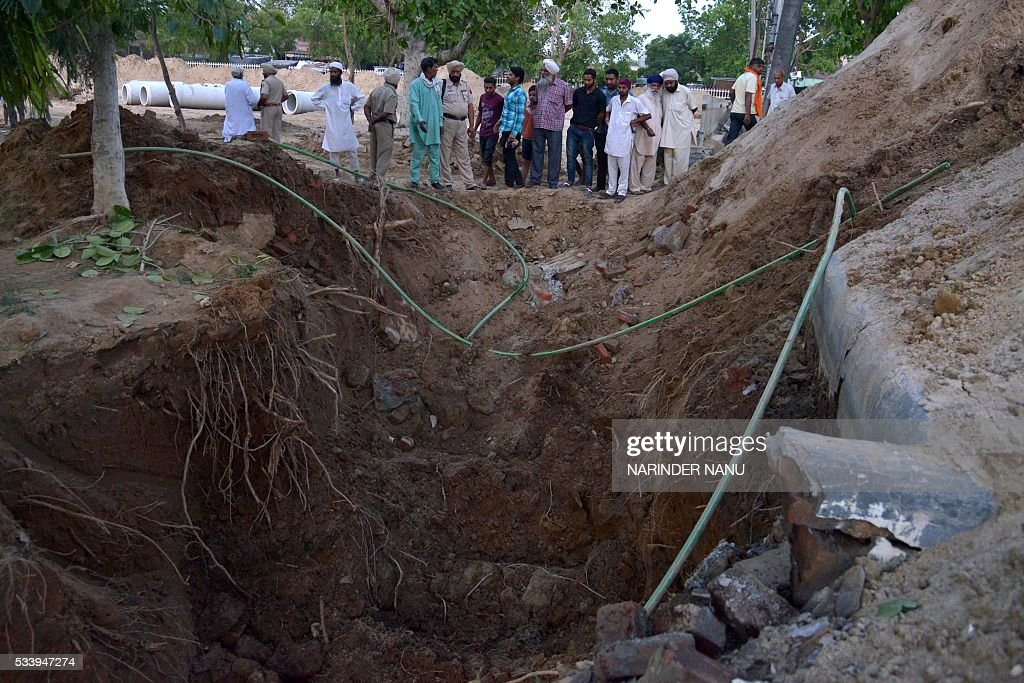 Indian police personnel and villagers look at a construction site in the village of Fatahpur on the outskirts of Amritsar on May 24, 2016, after the death of three labourers. Three labourers were killed in the northern Indian city as mud collapsed ontop of them while they dug soil for a sewage system at a new central jail. / AFP / NARINDER