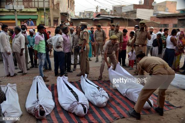 Indian police personnel arrange the bodies of victims outside a hospital in Etah some 35kms south of Agra on May 5 after a traffic accident in the...