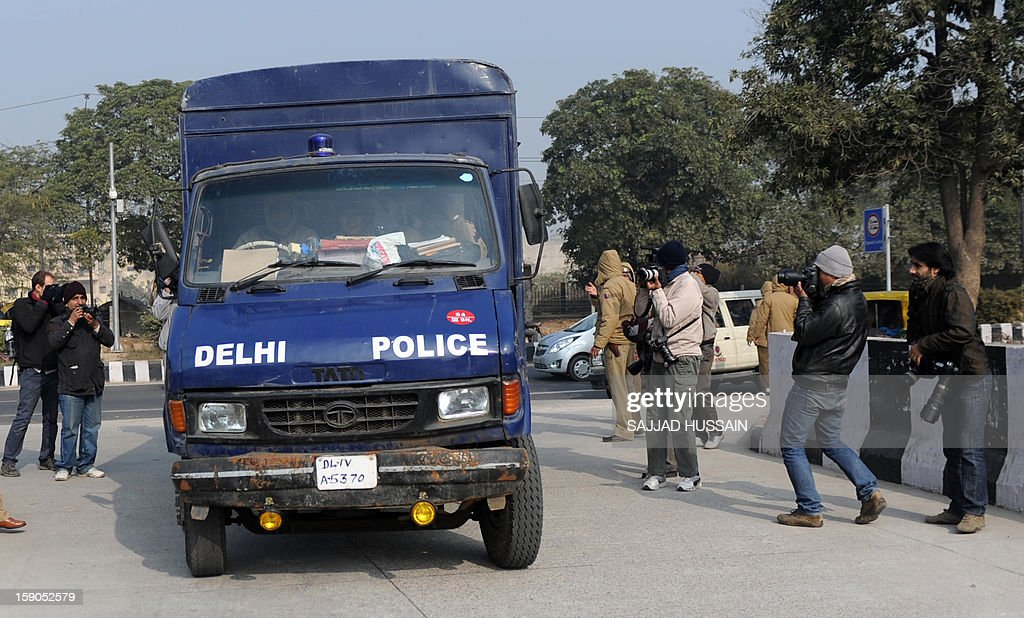 Indian police personnel drive a vehicle, which is believed to be carrying the accused in a gangrape and murder case, at an entrance to Saket District Court in New Delhi on January 7, 2013. Five men charged with the brutal gang-rape and murder of a student in New Delhi will appear in court for the first time after police said they had forensic evidence to link them to the killing. AFP PHOTO/SAJJAD HUSSAIN