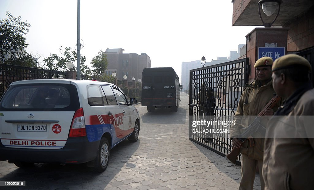 Indian police personnel escort a vehicle, which is believed to be carrying the accused in a gangrape and murder case, at an entrance to Saket District Court in New Delhi on January 7, 2013. Five men charged with the brutal gang-rape and murder of a student in New Delhi will appear in court for the first time after police said they had forensic evidence to link them to the killing.