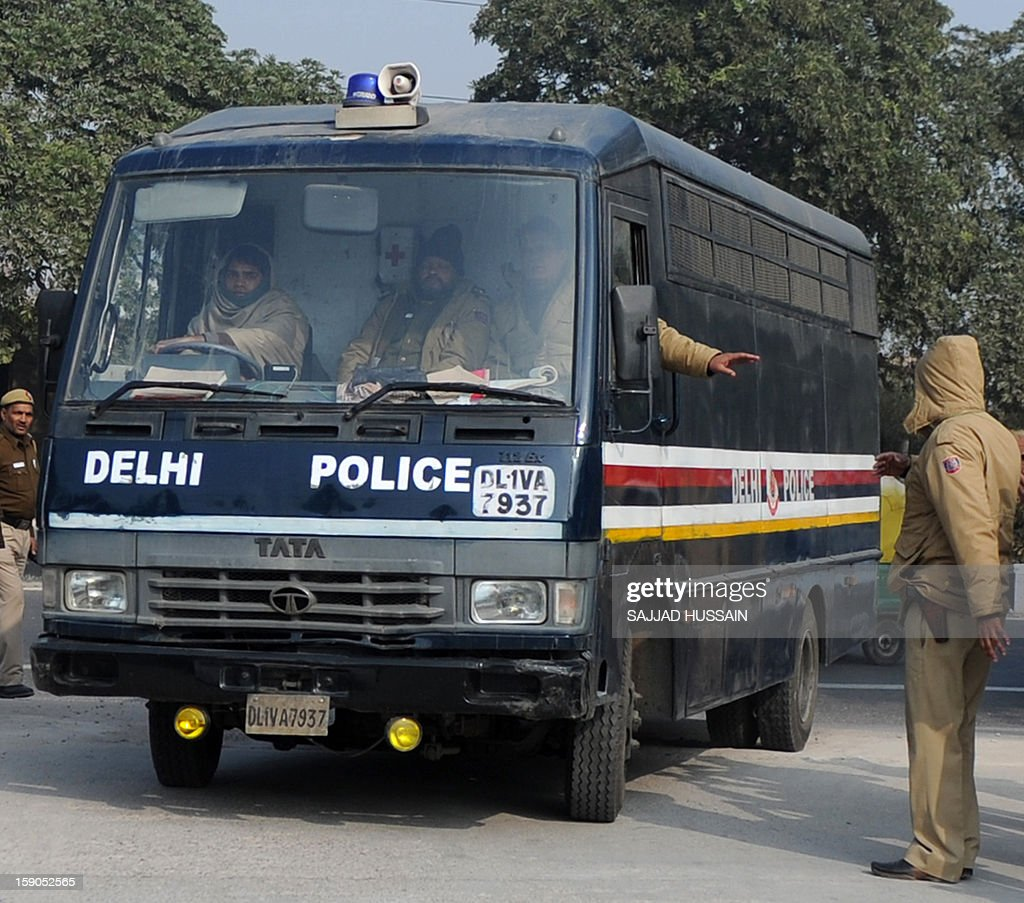 Indian police personnel guide a vehicle, which is believed to be carrying the accused in a gangrape and murder case, at an entrance to Saket District Court in New Delhi on January 7, 2013. Five men charged with the brutal gang-rape and murder of a student in New Delhi will appear in court for the first time after police said they had forensic evidence to link them to the killing. AFP PHOTO/SAJJAD HUSSAIN