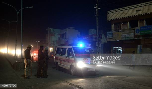 Indian police personnel look as an ambulance passes through a cordon some 4kms from the ashram of 'Godman' Rampal Maharaj in Hisar some 175...