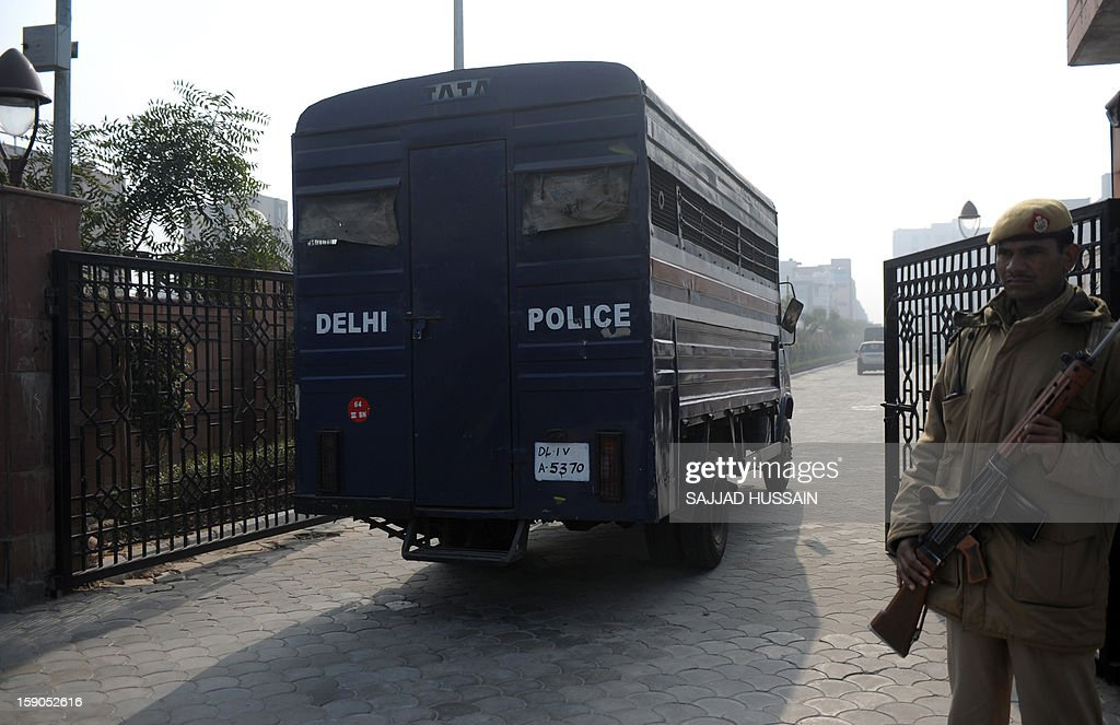 Indian police personnel look on as a vehicle, which is believed to be carrying the accused in a gangrape and murder case, arrives at an entrance to Saket District Court in New Delhi on January 7, 2013. Five men charged with the brutal gang-rape and murder of a student in New Delhi will appear in court for the first time after police said they had forensic evidence to link them to the killing.