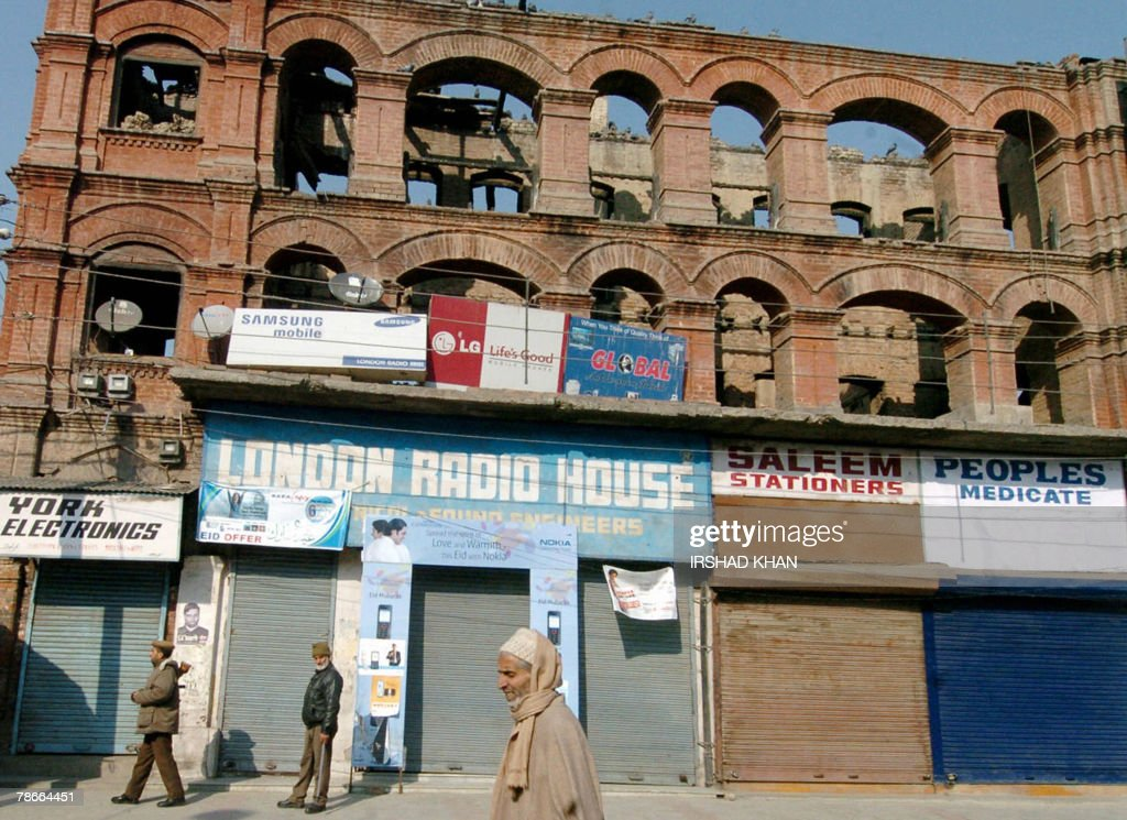 Indian police personnel patrol a row of shuttered shops as an elderly Kashmir pedestrian walks past during a strike in Srinagar, 28 December 2007, called by hardline Pro-Pakistan separatist leader and chairman of a faction of The Hurriyat Conference Syed Ali Shah Geelani to protest the killing of former Pakistani Prime Minister Benazir Bhutto. Former Premier Bhutto was killed 27 December, in a suicide attack following a campaign rally in Rawalpindi. Pakistan's interior ministry said that it was 'unaware' of Al-Qaeda claiming a link to Benazir Bhutto's killing but said 'extremist elements' behind a wave of attacks this year could be responsible AFP PHOTO/Irshad KHAN