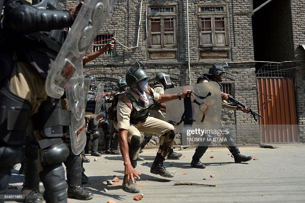 Indian police personnel prepare to throw stones towards Kashmiri protestors during clashes in Srinagar on July 1, 2016. Police fired teargas shells and rubber bullets to disperse Kashmiris protesting against Indian rule after the last Friday prayers of Ramadan near the main Jamia Masjid mosque. Several rebel groups have for decades been fighting Indian forces deployed in the region, seeking independence or a merger of the territory with Pakistan. MUSTAFA