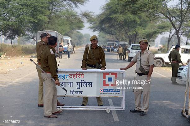 Indian police personnel stand at a check point near the ashram of selfstyled 'godman' Rampal Maharaj at Barwala in the district of Hisar some 175...