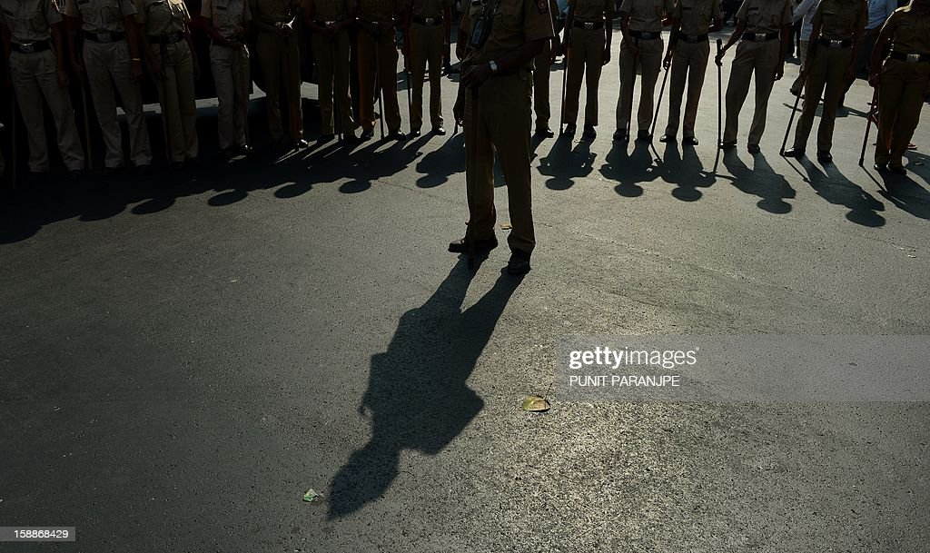 Indian police personnel stand during during a protest by slum dwellers in Mumbai on January 2, 2013. Around two thousand slum dwellers took part in the protest to demand housing rights for the poor from the government.