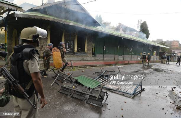 Indian police personnel stand near the burning railway station during an indefinite strike called by separatist group Gorkha Janamukti Morcha in...