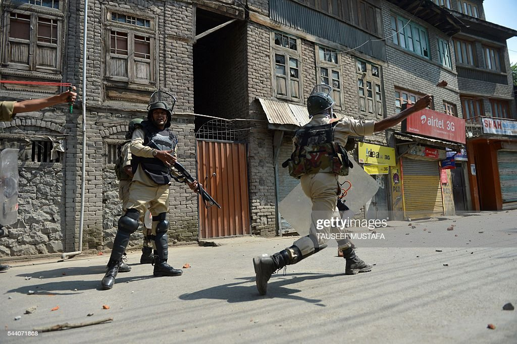 Indian police personnel throw stones towards Kashmiri protestors during clashes in Srinagar on July 1, 2016. Police fired teargas shells and rubber bullets to disperse Kashmiris protesting against Indian rule after the last Friday prayers of Ramadan near the main Jamia Masjid mosque. Several rebel groups have for decades been fighting Indian forces deployed in the region, seeking independence or a merger of the territory with Pakistan. MUSTAFA