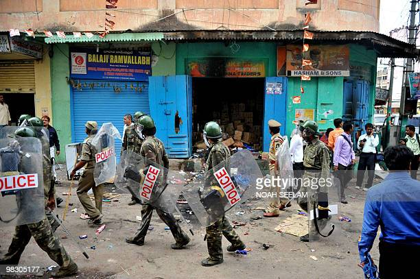 Indian police personnel walk past a grocery shop which was burnt during communal violence at Begum Bazar in Hyderabad on March 30 2010 Indian police...