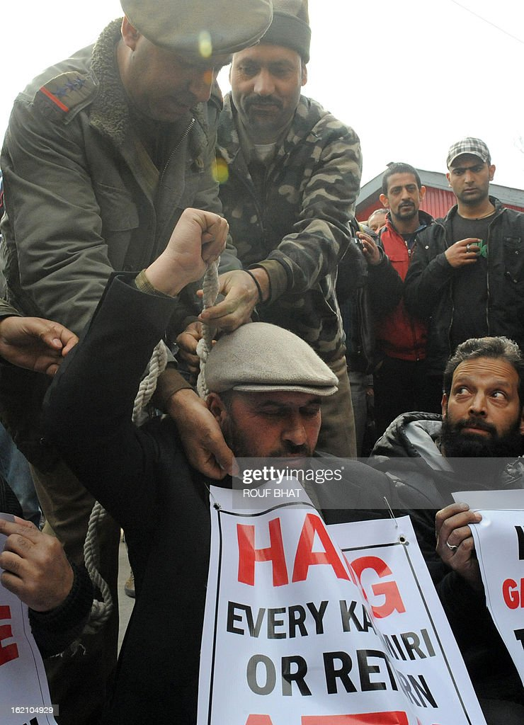 Indian police remove a noose from the neck of Kashmiri human rights activist Ashan Untoo,who was depicting a hanging during a protest in Srinagar on February 18,2013. Untoo demanded the return of Afzal Guru's mortal remains to his family in Kashmir. Guru was executed on February 9, 2013 and buried inside a high security prison in New Delhi over his role in a deadly attack on Indian parliament in New Delhi in 2001. AFP PHOTO/ Rouf BHAT