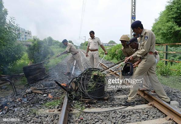 Indian police remove bundles of cables left burning by rioters as they clear railway tracks on the outskirts of Ahmedabad on August 26 2015 Thousands...