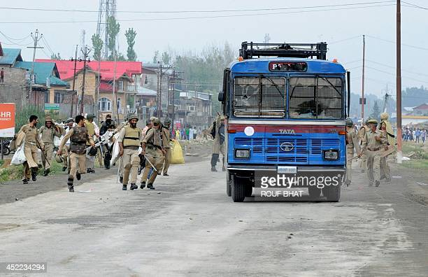 Indian police run toward their van as they clash with Kashmiri protesters on the outskirts of Srinagar on July 162014 Six people were killed and two...
