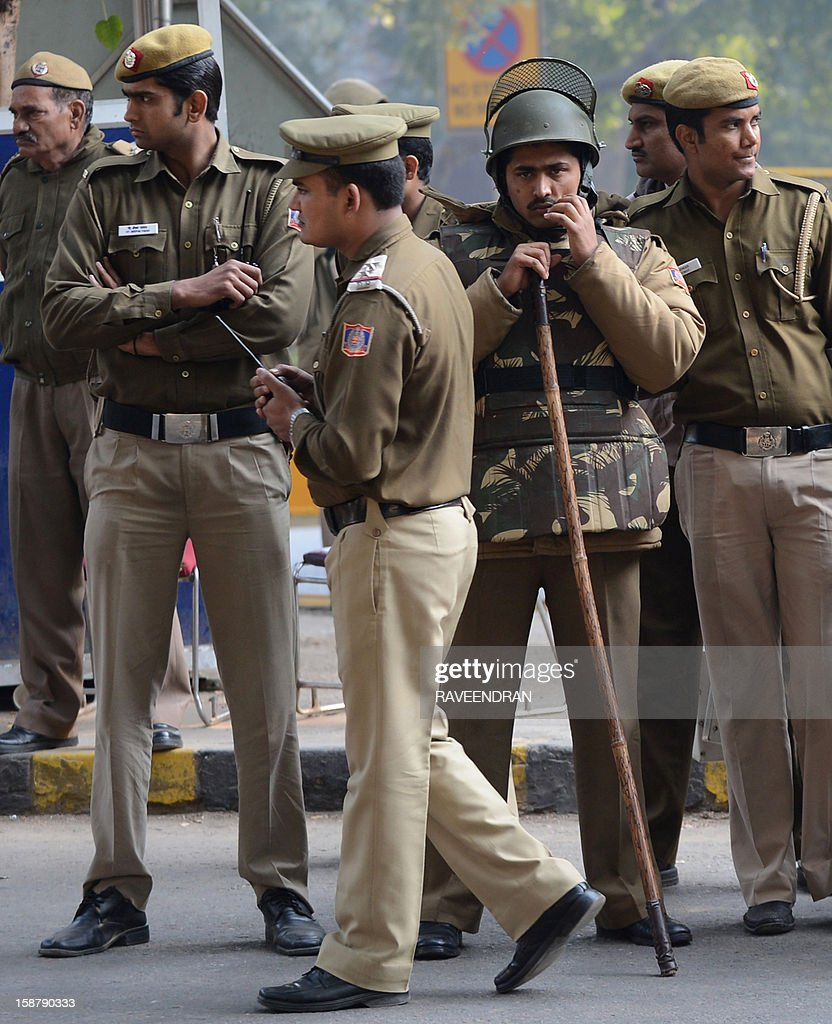 Indian police stand alert on a street in New Delhi on December 29, 2012, as Indian leaders appealled for calm fearing fresh outbursts of protests after the death of a gang-rape victim. New Delhi's top police officer and chief minister have urged people to mourn the death of a gang-rape victim in a peaceful manner as large parts of the city-centre were sealed off. The calls for calm came after an Indian woman who was gang-raped on a New Delhi bus died in a Singapore hospital after suffering severe organ failure.