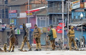 Indian police stand guard at a barbed wire roadblock during a curfew in Srinagar on February 9 2014 Authorities in Indian Kashmir imposed curfew in...