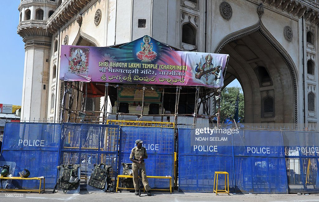 Indian police stand guard in front of the Bhagayalakshmi temple alongside the historic monument Charminar in the old city of Hyderabad on November 17, 2012. Restrictions were lifted on the movement of people and vehicular traffic around Charminar, where a mob indulged in stone pelting and trouble broke out after the noon prayers following the controversy over the newly erected structure near the Bhagyalaxmi temple. Muslims, supported by the Majlis-e-Ittehadul Muslimeen (MIM) party, opposed the move fearing that the temporary structure would pave the way for the permanent construction of a larger temple near the Charminar monument. AFP PHOTO / Noah SEELAM