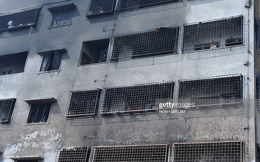 Indian police stand inside a residential apartment that caught fire on the outskirts of Hyderabad on November 26, 2012. Five people including a child died in the blaze, which allegedly started when a makeshift shed nearby burned. AFP PHOTO / Noah SEELAM