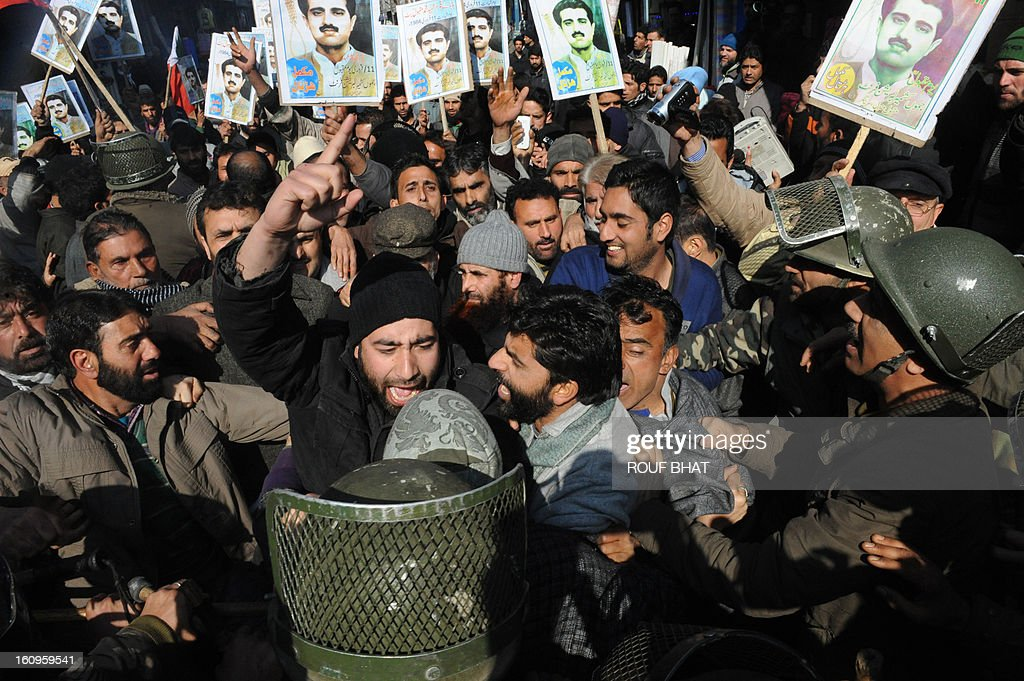 Indian police stop members of pro-independence group Jammu and Kashmir Liberation Front (JKLF) as they shout slogans and hold photographs of their founder leader Maqbool Bhat at a protest march during which a number of activists were arrested in Srinagar on February 8, 2013. The group were demanding the return of the remains of their founding leader, Maqbool Bhat who was hanged in an Indian jail in February 11, 1984 and buried there. AFP PHOTO/Rouf BHAT